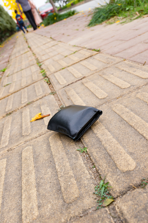 lost wallet on sidewalk with people going far away Banco de Imagens