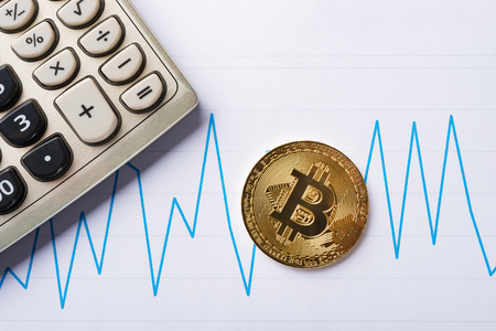 bitcoins and caculator on a chart as financial concept Reklamní fotografie