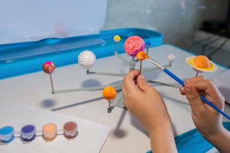 Kind Malerei die Erde auf einem Sonnensystem Modell Standard-Bild - 99268304
