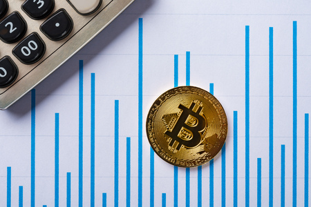 bitcoins and caculator on a chart as financial conceptbitcoins and caculator on a chart as financial concept