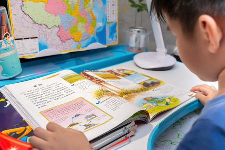 Zhongshan,China-May 19, 2018:Chinese kid reading books about nature at home. Editorial