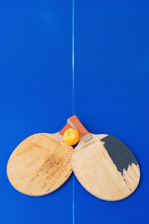 pair of old table tennis rackets and a dented ball on a blue table tennis table