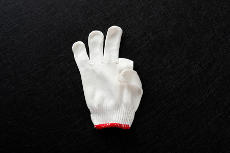 white glove with gesture of OK on black background