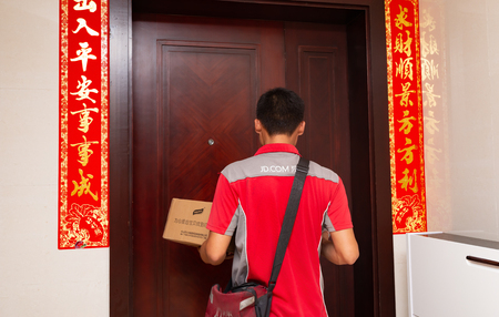 Zhongshan,China-June 3,2018:male courier from JD.com delivering a parcel to the customers home.June 18 is the birthday of JD and there are lots of big sales in June.