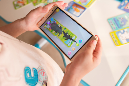 Zhongshan,China-April 22,2018:kid playing Augmented Reality popup of elephant and crocodile via mobile. AR and VR games become more and more popular.