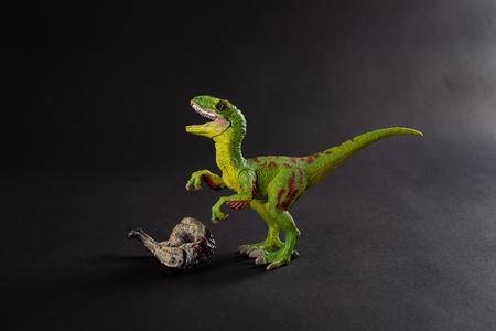 velociraptor with a dinosaur body nearby on dark background