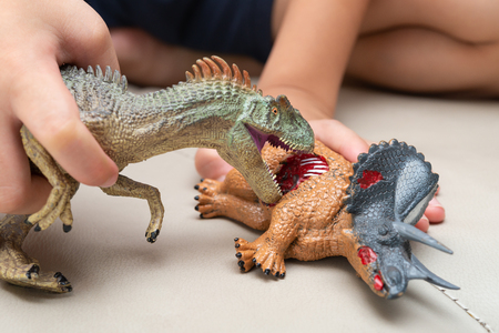 kid playing with toys of allosaurus and triceratops bloody body on sofa at home Stock Photo