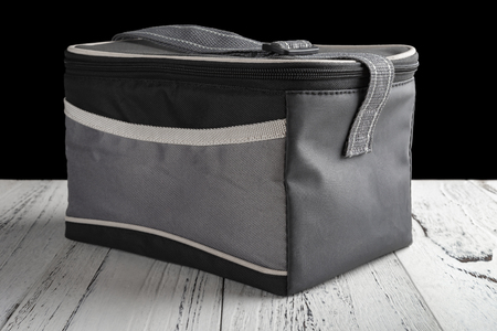 grey and black lunch pack carrier on a wood table on black background 免版税图像