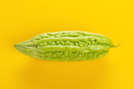 fresh green bitter melon on a yellow background