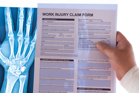 man reading a work injury claim form with a wrapped hand on top of an X-ray film medical and insurance concept