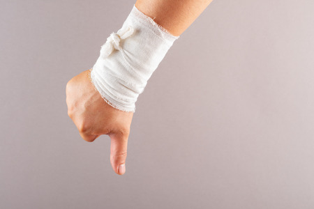 nagative gesture of thumbs down by a wrapped hand