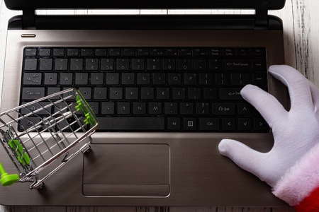 santa claus using a laptop with a shopping cart nearby
