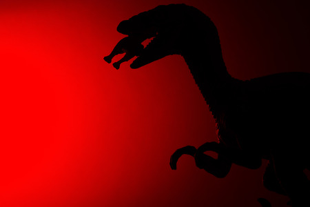 shadow of Deinonychus biting a smaller dinosaur with red light in dark Stock Photo
