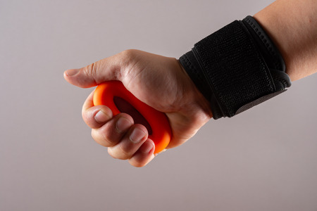 hand with a wrist protective strap doing exercises by squeezing an O ring hand trainer