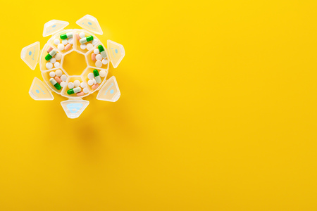 top view daily doses pills in a plastic container on yellow background with copy space Stock Photo