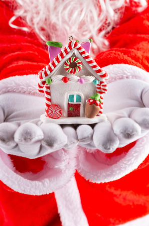 Santa Claus hands holding a house model with Christmas decoration