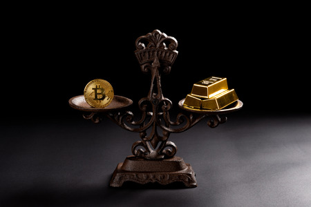 bitcoin and gold bars on a balanced scale concept of the value of bitcoins Archivio Fotografico