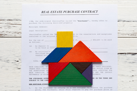 top view real estate purchase contact with tangram shaped as a house 版權商用圖片