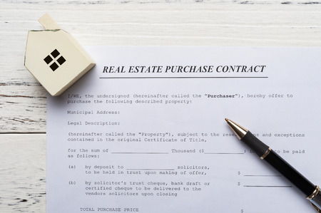 top view real estate purchase contact with an architectural model and a pen