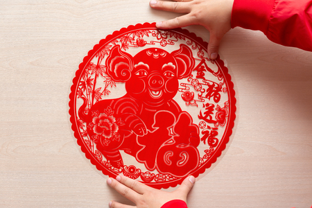 sticking a fluffy red flat paper-cut sticker as symbol of Chinese New Year of the pig the Chinese means good luck and the pig gives you fortune