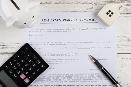 top view real estate purchase contact with a house and piggy bank and calculator and a pen
