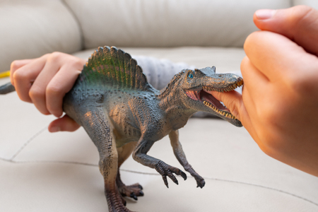 kid playing a spinosaurus toy and putting his finger inside the mouth