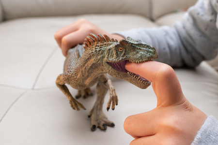 kid playing a allosaurus toy and putting his finger inside the mouth