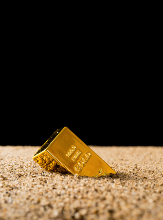 gold half sank into the sand in front of a black background concept of value collapsing of the gold Stock Photo