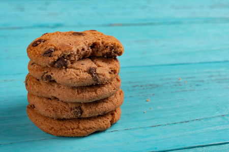 stack of sweet cookies on blue background and the top one with a bite Stock Photo
