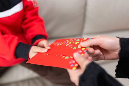 Mutter gibt ihrem Sohn eine rote Tasche red