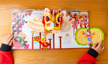 Zhongshan,China-January 26,2019:kid reading 3D books introducing cultures about Chinese new year at home Editorial