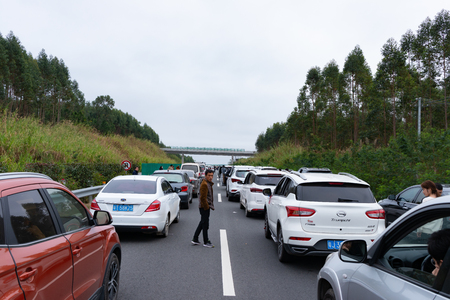 Guangxi,China-February 10,2019:tailbacks on the last holiday of the Chinese new year.Cars cannot move a little bit so people get out of the cars and keep waiting.