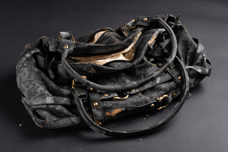 moldy leather bag on dark background