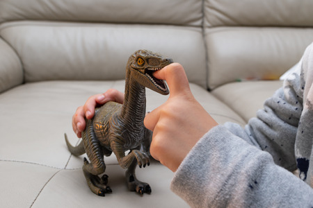 kid playing a Deinonychus toy and putting his finger inside the mouth
