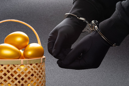 arrested man in handcuffs in front of a basket with gold eggs Stock Photo