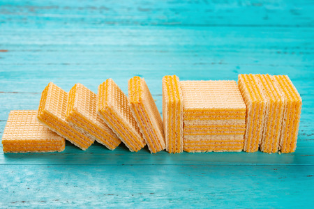 side view of cheese wafer blocks on blue background