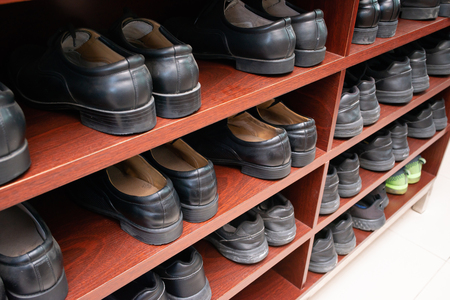 unified black leather shoes on shelf
