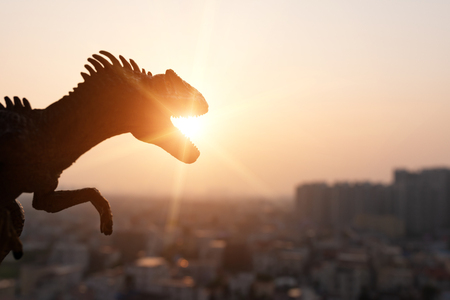 silhouette of allosaurus and buildings in sunset time Stock Photo