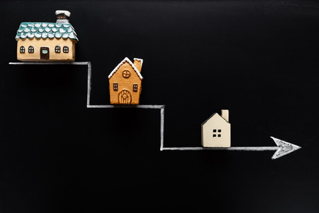 going down arrow with samller and smaller houses on blackboard background Stock Photo