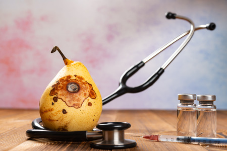 rotten pear surrounded by stethoscope