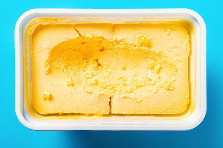 top view box of mango flavor ice cream with some digged out on blue background Imagens