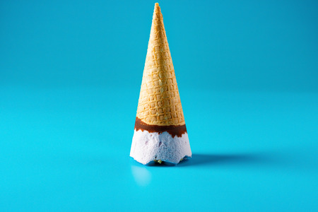 peanut ice cream cone upside down stands on blue background