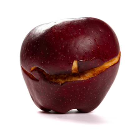 overripe apple with a crack on white background