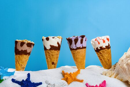 white sand with different ice cream cones and starfishes concept of summer holidays