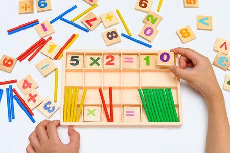 Kind macht Multiplikationsgleichung mit Zählstäben Standard-Bild