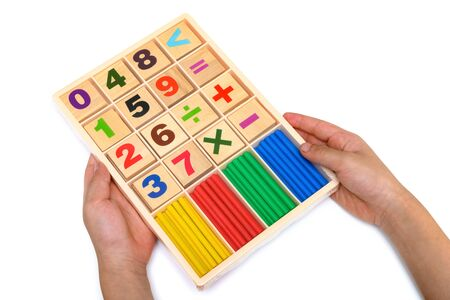kid holding set of counting rods with number plates on white
