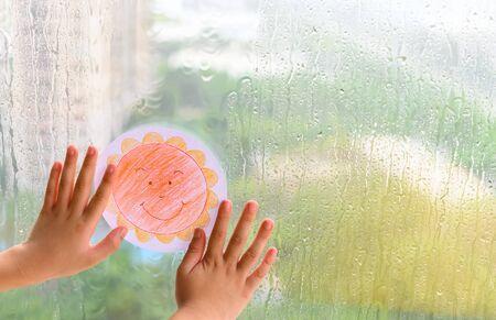 bambino che tiene l'immagine di un sole sorridente in un giorno di pioggia concetto di fede e ottimismo