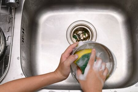 boy washing dishware in the kitchen sink with soapy sponge Stock Photo