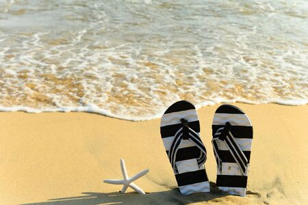 pair of slippers and a starfish in front of a beach with wave coming