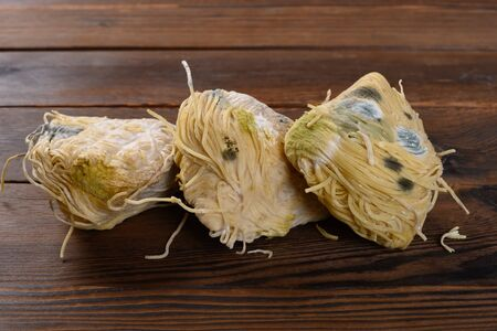 moldy noodles on a wood table